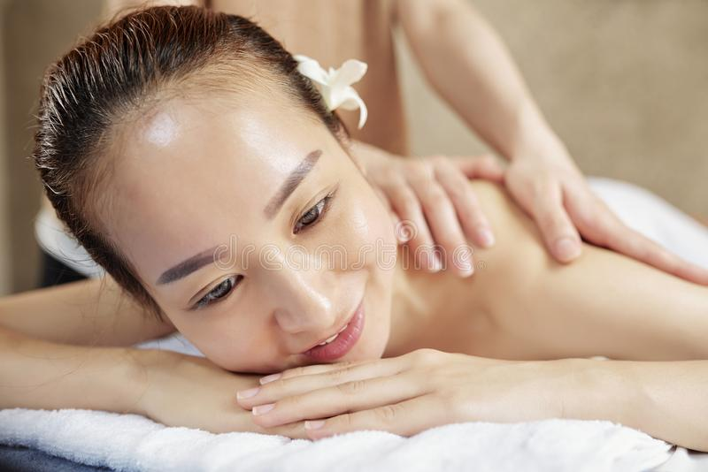 Asian woman enjoying back massage royalty free stock images