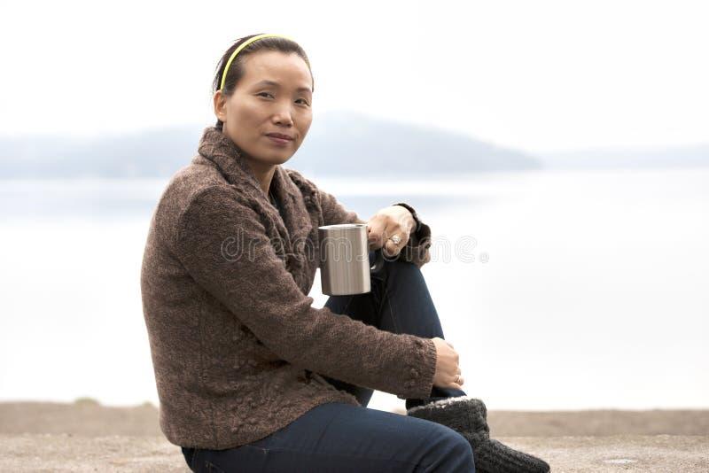 Asian woman enjoys coffee by lake. stock photography