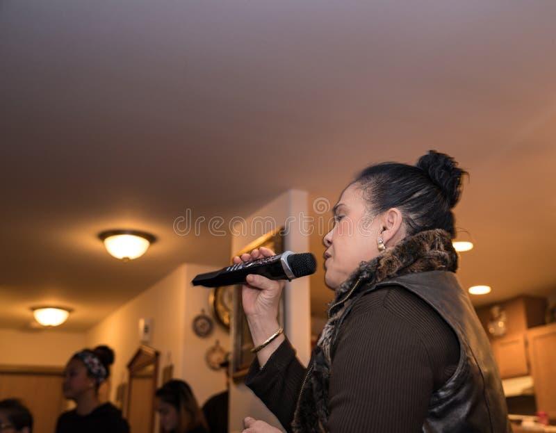 Asian woman singing karaoke at a party royalty free stock photo