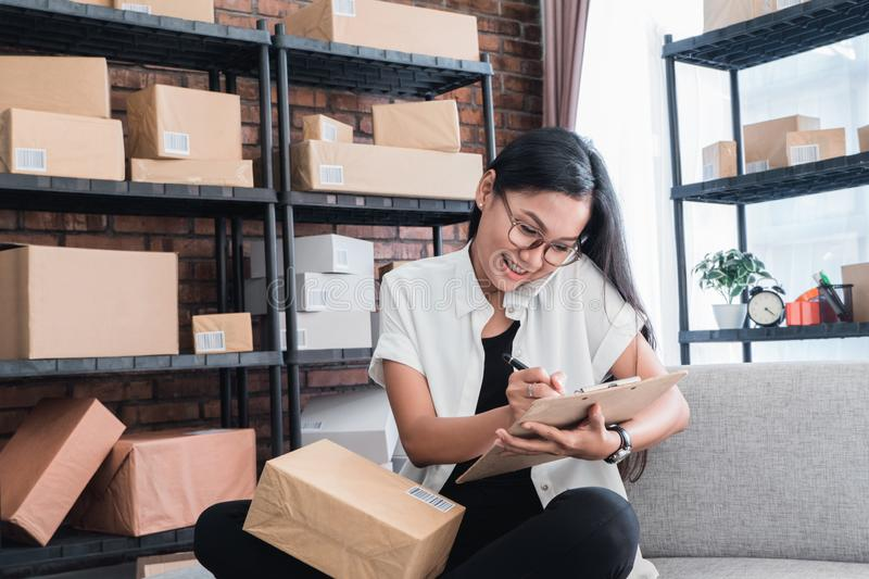 Asian woman entrepreneur online seller. Asian woman entrepreneur receiving online order via phone call at home stock photo