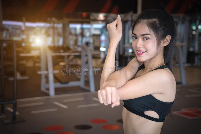 Asian woman exercising in gym. Young sports girl stretching exercises at fitness. royalty free stock photography
