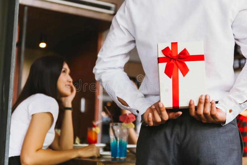 Asian woman expected to receive a surprise present gift box from man as a romantic couple for occasional anniversary celebration. royalty free stock images