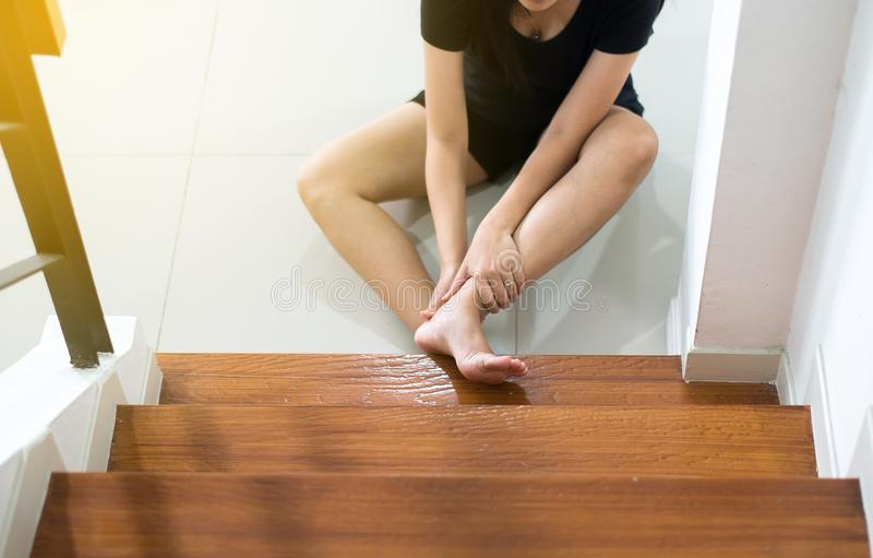 Asian woman falling down of stair,Hand female touching her legs injured royalty free stock photos