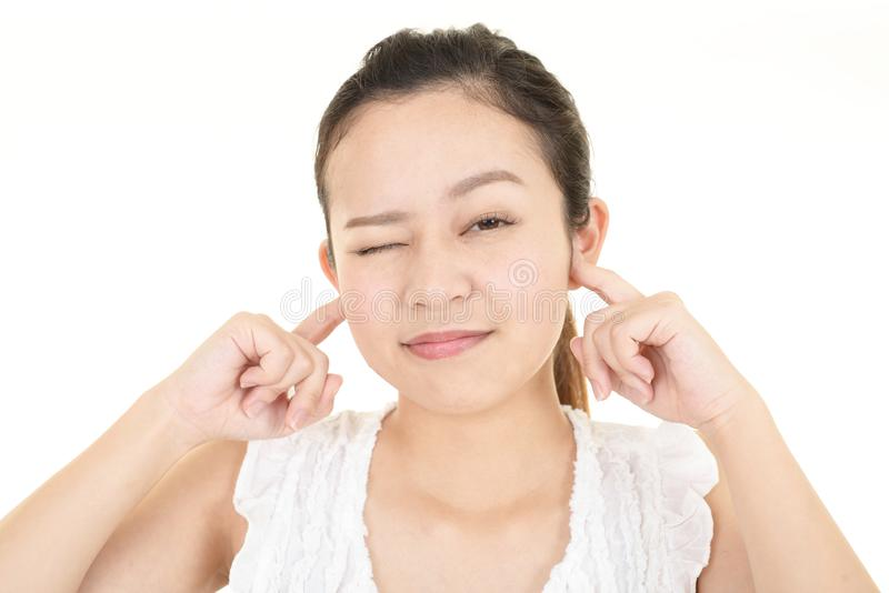 Woman closing ears. Asian woman is feeling stressed royalty free stock photo