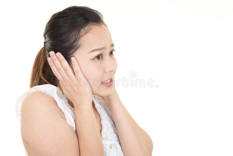 Woman who holds her ears stock image