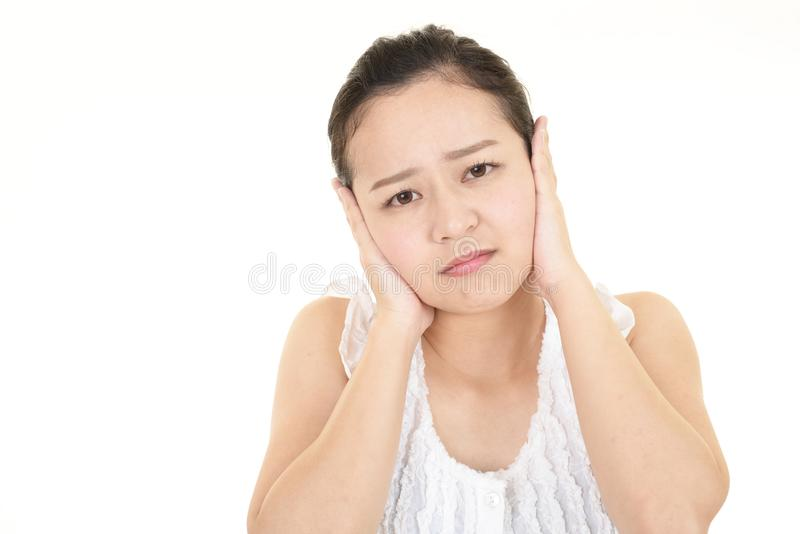 Woman who holds her ears royalty free stock photography