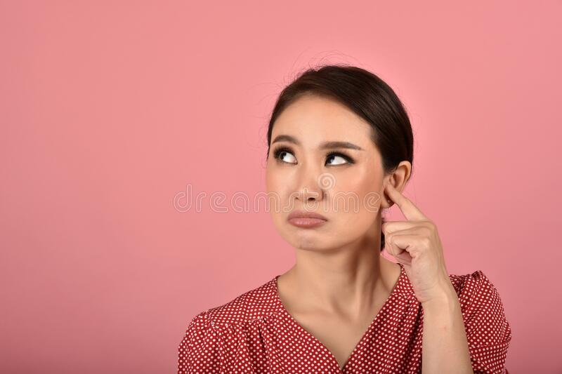 Asian woman feeling upset and frustrated, Girl rolling eyes with boredom and annoy about gossip. Asian woman feeling upset and frustrated, Girl rolling eyes stock images