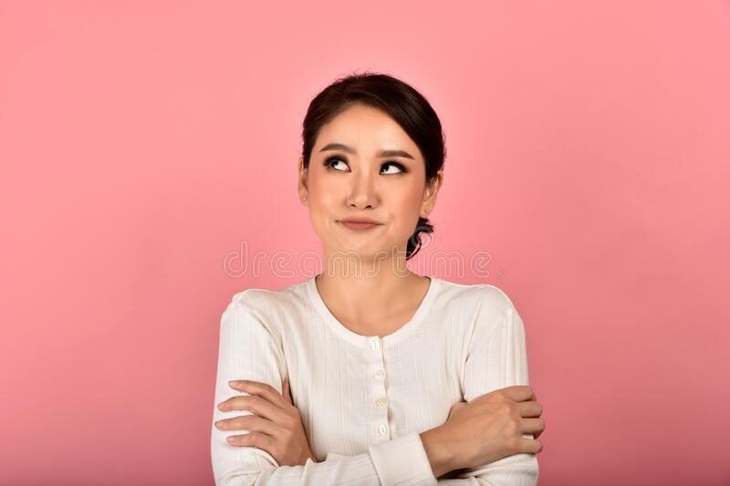 Asian woman feeling upset and frustrated, Girl rolling eyes with boredom and annoy about gossip. Face expression and body gesture stock image
