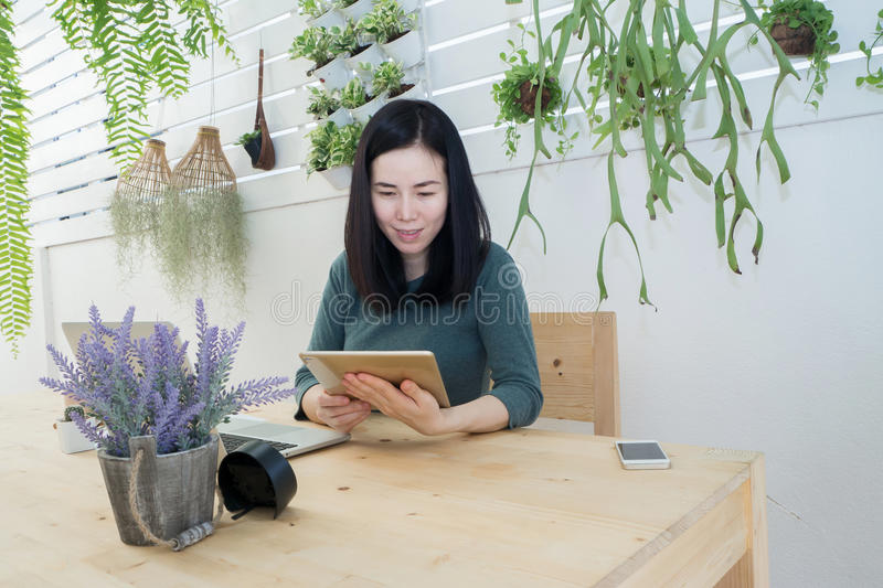 Asian woman finding data on tablet at tree garden, relax time on. Office corner, shopping online concept at home. woman find job on tablet at home royalty free stock photo