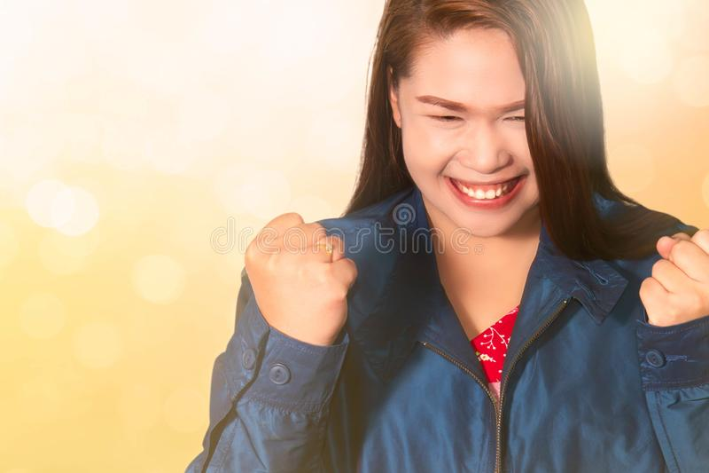 Asian woman with fists raised up gesture,  successful, celebrating victory,achievement and winning. Asian woman with fists raised up gesture on blurred bokeh royalty free stock photos