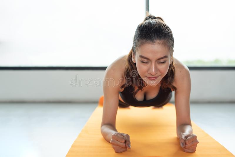 Asian woman fitness girl do plank at fitness gym on yoga mat. He stock photography