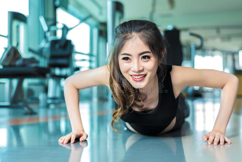 Asian woman fitness girl do pushing ups at fitness gym. Healthcare and Healthy concept. Training and Body build up theme. royalty free stock photos