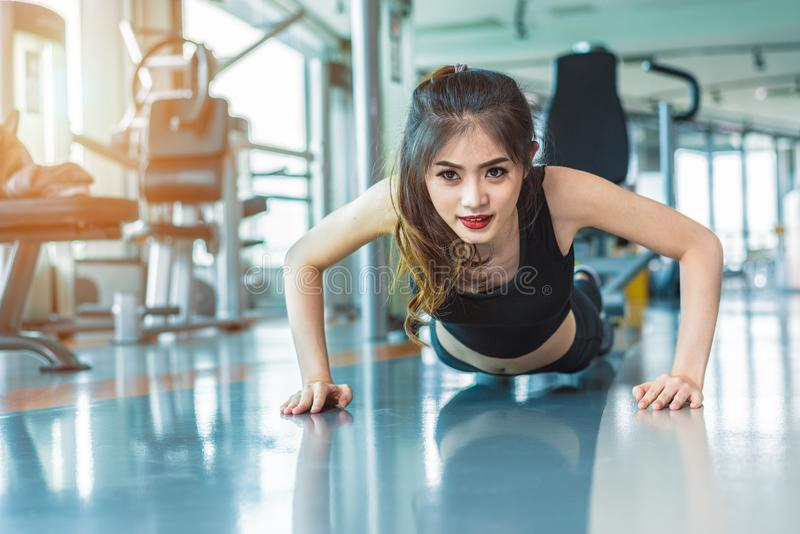 Asian woman fitness girl do pushing ups at fitness gym. Healthcare and Healthy concept. Training and Body build up theme. Strength and Beauty concept royalty free stock image