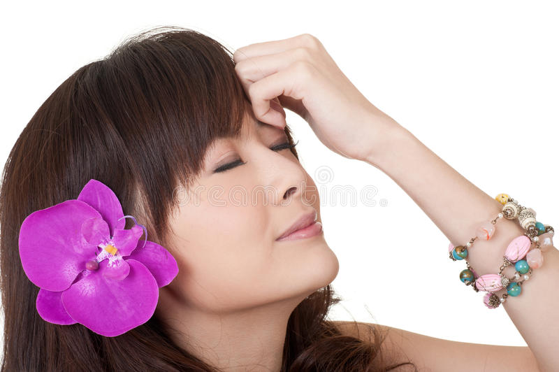 Asian woman with flower. On head, closeup portrait on white stock image