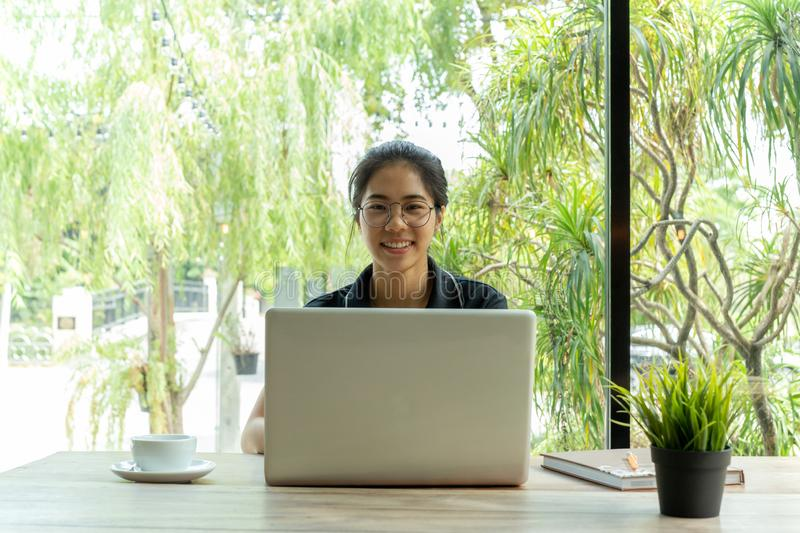 Asian woman with glasses smiling using laptop with cup of coffee on the table. royalty free stock photo