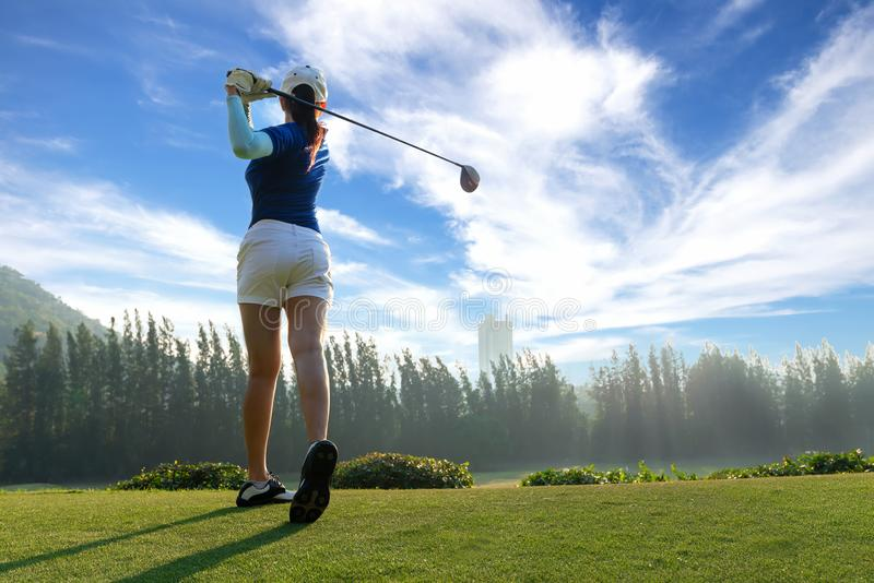 Asian woman golf player doing golf swing tee off on the green evening time in the blue sky background. She presumably does exerci. Se. Healthy and Lifestyle royalty free stock photography