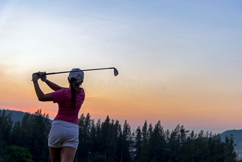 Asian woman Golf player hit swing shot golf ball on the green sunset of green club in evening time. royalty free stock image