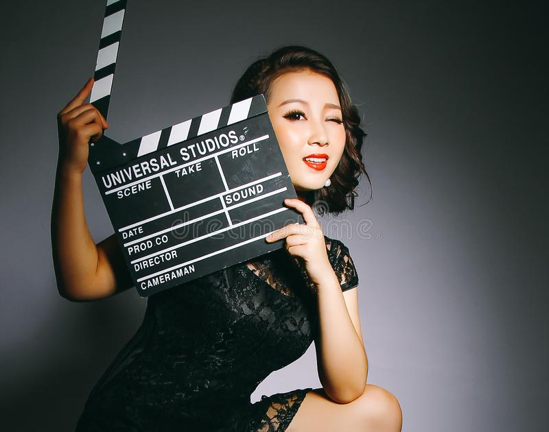 Asian women wear cheongsams and carry movie boards stock image