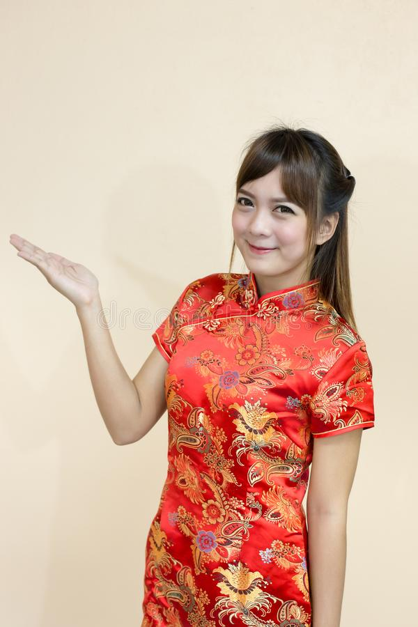 Asian woman greeting in traditional chinese or cheongsam with hand asian woman greeting in traditional chinese or cheongsam with hand lift welcome expression and lucky in chinese new year celebration in red golden style m4hsunfo