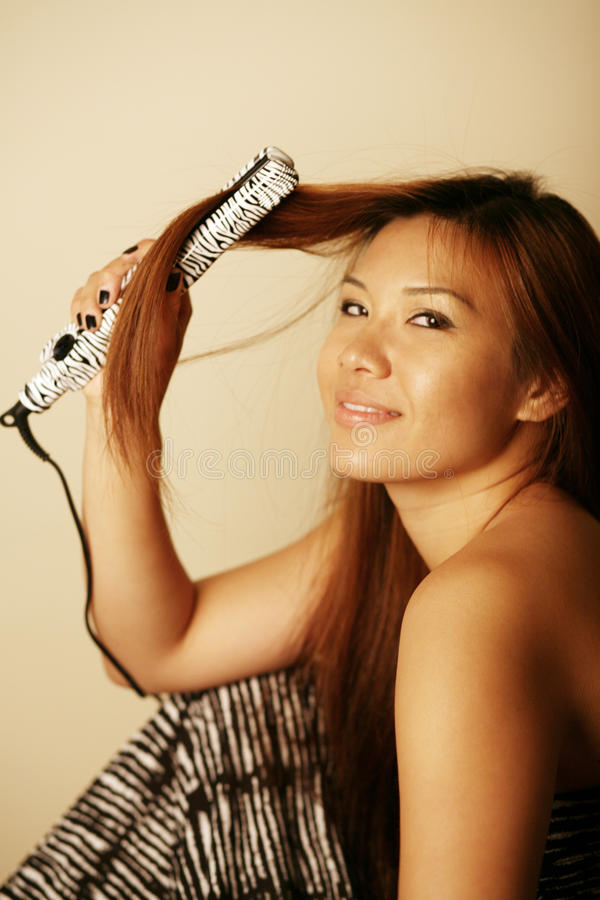 Download Asian Woman With Hair Straightener Stock Image - Image: 10468363