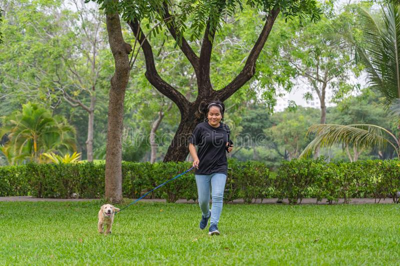 Asian woman happily jogging with her little golden puppy royalty free stock photo