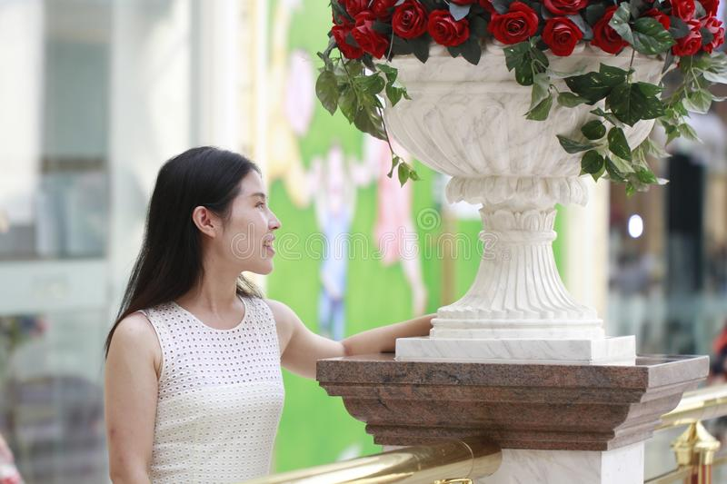 Asian Woman happily rise her head smile looking flower. Asian Woman happily rise her head smile looking ,Stand on the edge of the corridor in the mall. Enjoy stock images