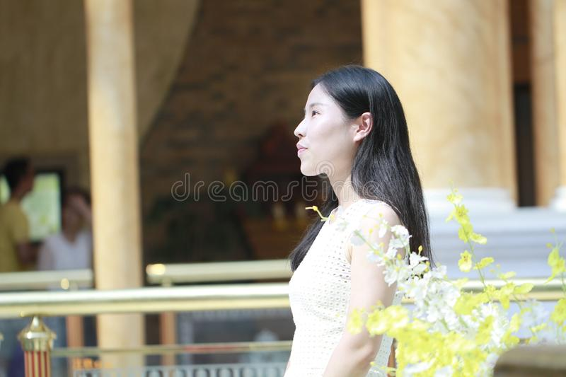 Asian Woman happily Wearing a white dress rise her head smile looking. Asian Woman happily rise her head smile looking In the flower,Standing in the corridor of royalty free stock photo