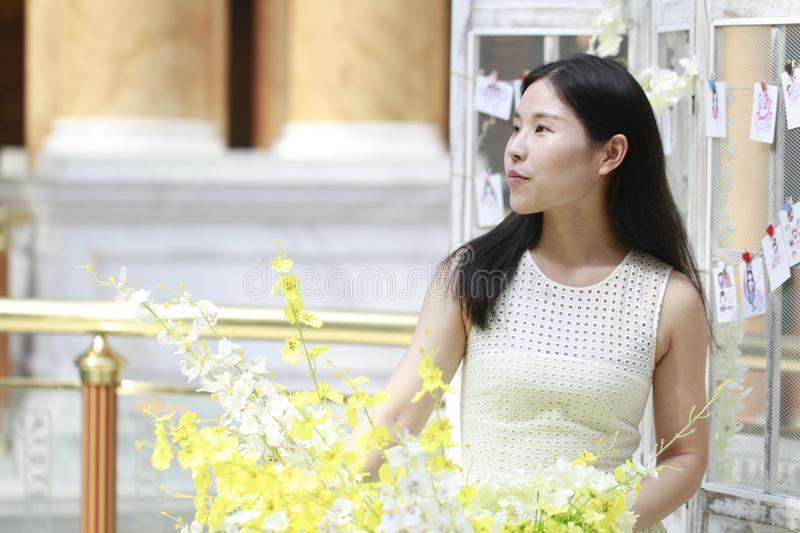 Asian Woman happily Wearing a white dress rise her head smile looking. Asian Woman happily rise her head smile looking In the flower,Standing in the corridor of royalty free stock images