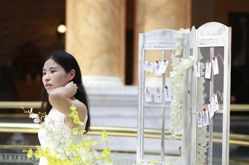 Asian Woman happily Wearing a white dress rise her head smile looking. Asian Woman happily rise her head smile looking In the flower,Standing in the corridor of royalty free stock photos