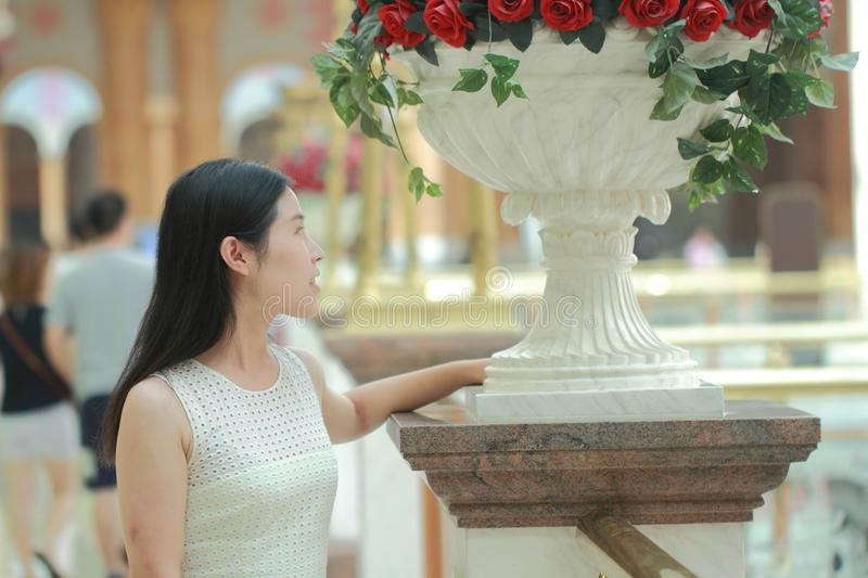 Asian Woman happily rise her head smile looking flower. Asian Woman happily rise her head smile looking ,Stand on the edge of the corridor in the mall. Enjoy royalty free stock photo