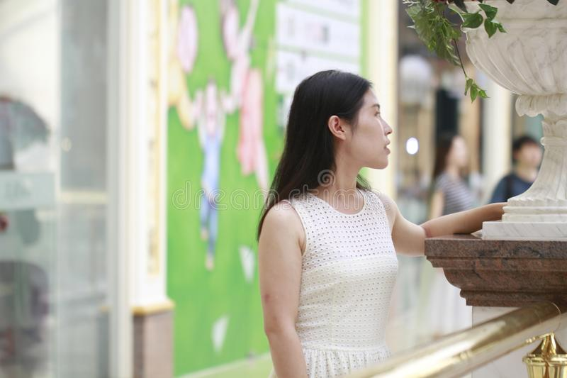 Asian Woman happily rise her head smile looking flower. Asian Woman happily rise her head smile looking ,Stand on the edge of the corridor in the mall. Enjoy royalty free stock photos