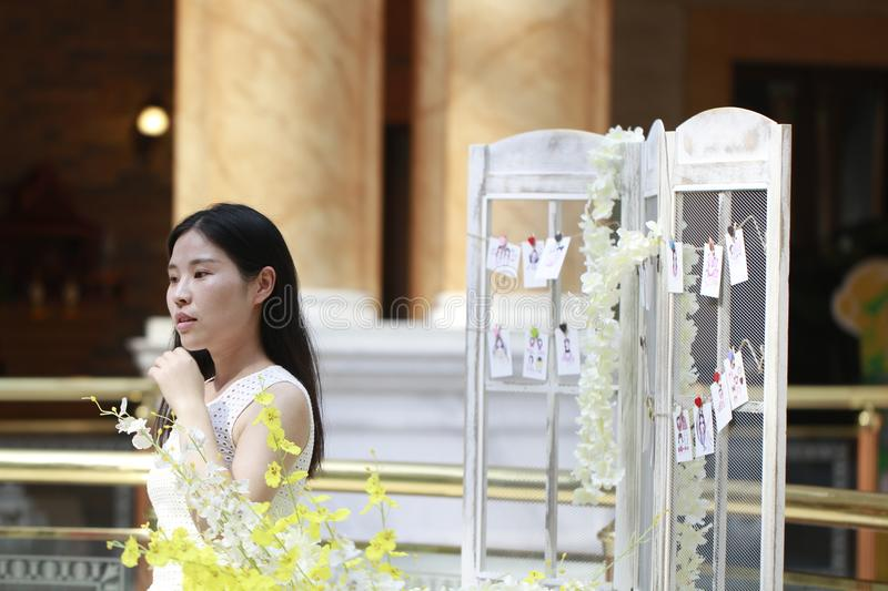 Asian Woman happily Wearing a white dress rise her head smile looking. Asian Woman happily rise her head smile looking In the flower,Standing in the corridor of stock photo