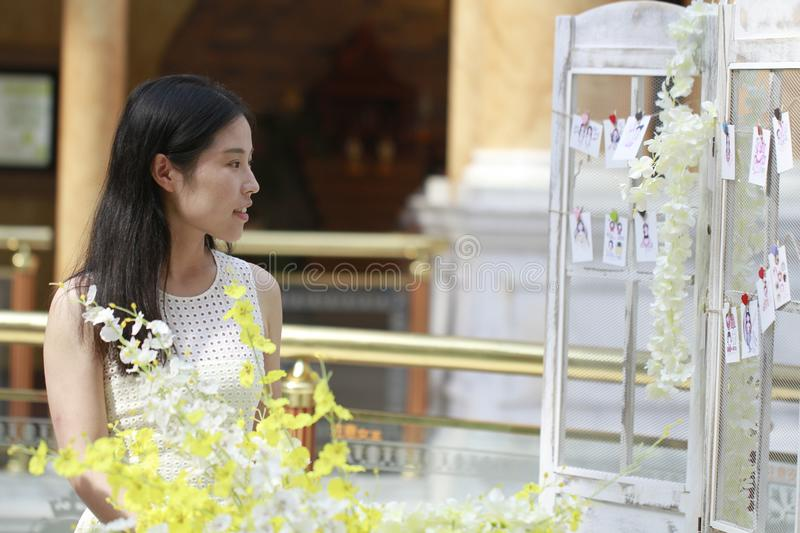 Asian Woman happily Wearing a white dress rise her head smile looking. Asian Woman happily rise her head smile looking In the flower,Standing in the corridor of royalty free stock image