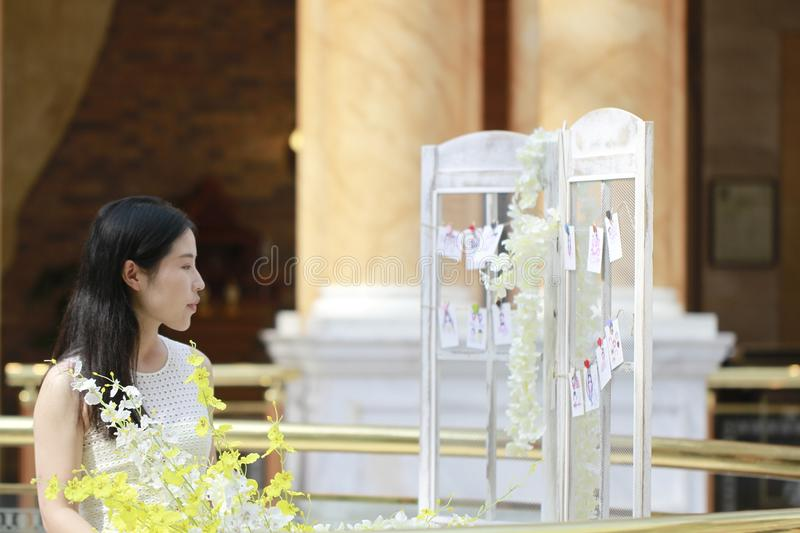 Asian Woman happily Wearing a white dress rise her head smile looking. Asian Woman happily rise her head smile looking In the flower,Standing in the corridor of stock photos