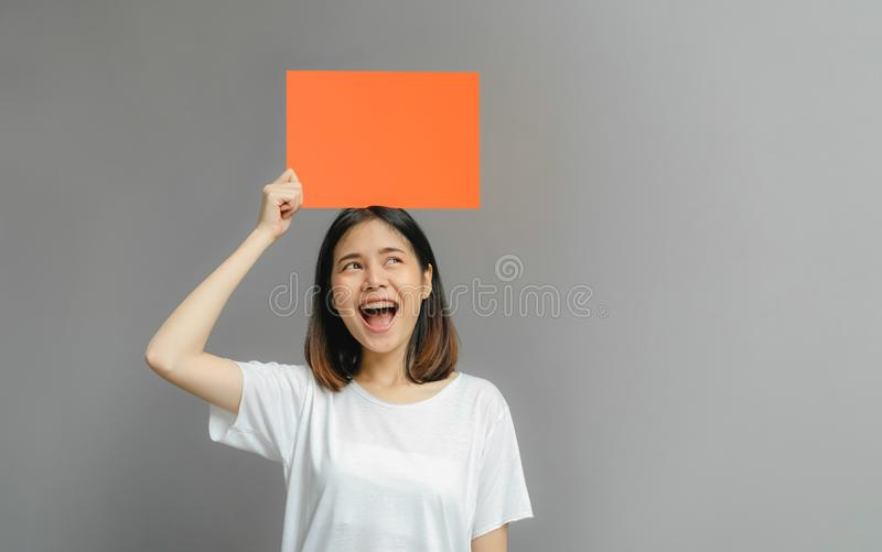 Asian woman of happy smiling holding a blank orange poster on gray background. With empty space for text royalty free stock image