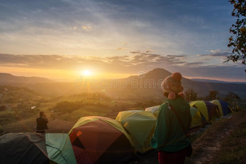 Asian woman happy and view relax during dramatic sunrise misty morning,Concept of outdoor camping adventure stock photo