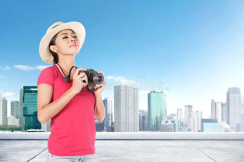 Asian woman in hat holding camera to take a picture of cityscapes royalty free stock photography