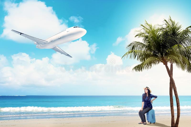 Asian woman in hat sitting on suitcase bag on the beach royalty free stock photo