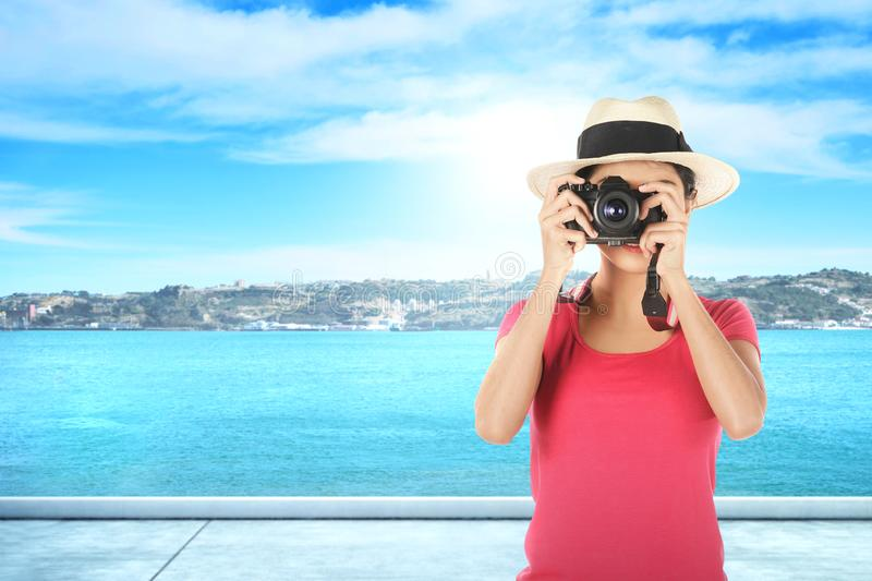 Asian woman in hat take a picture with her camera royalty free stock photos