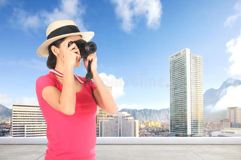 Asian woman in hat takes a picture of the modern city with her camera royalty free stock images