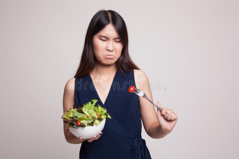 Asian woman hate salad. Asian woman hate salad on gray background royalty free stock photography