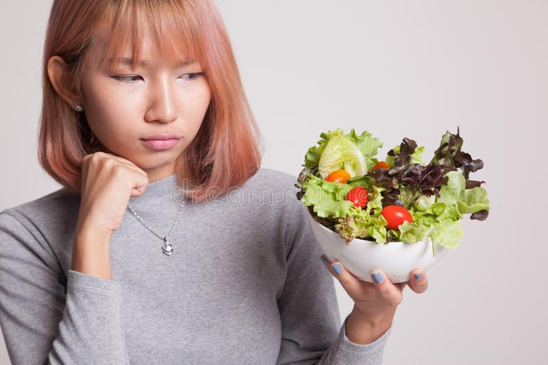 Asian woman hate salad. Asian woman hate salad on gray background stock image