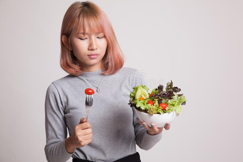 Asian woman hate salad. Asian woman hate salad on gray background royalty free stock image