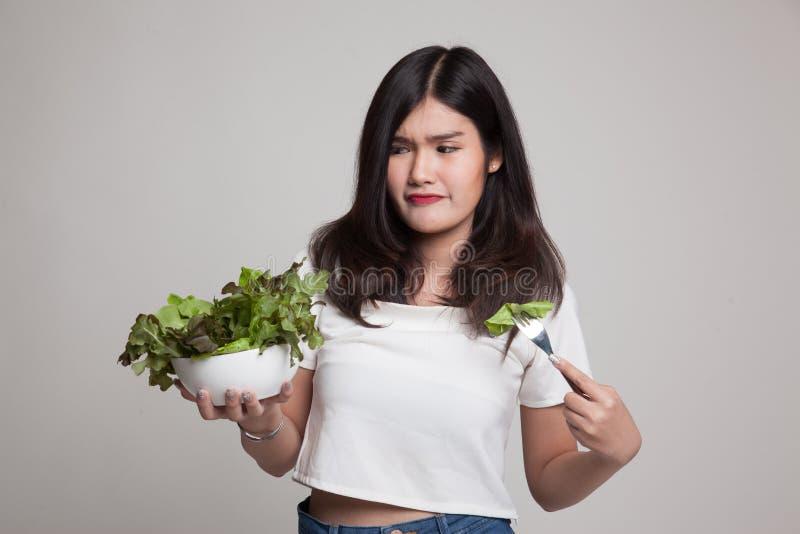 Asian woman hate salad. Asian woman hate salad on gray background stock photo