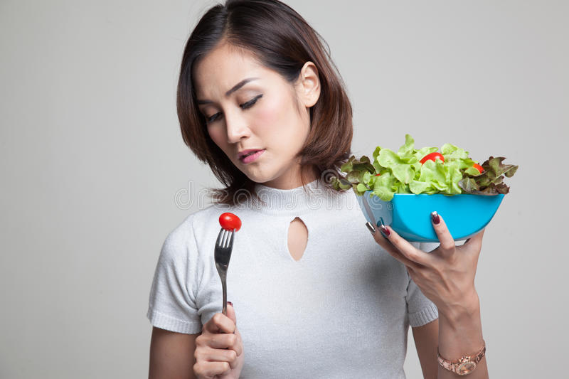 Asian woman hate salad. Asian woman hate salad on gray background stock images