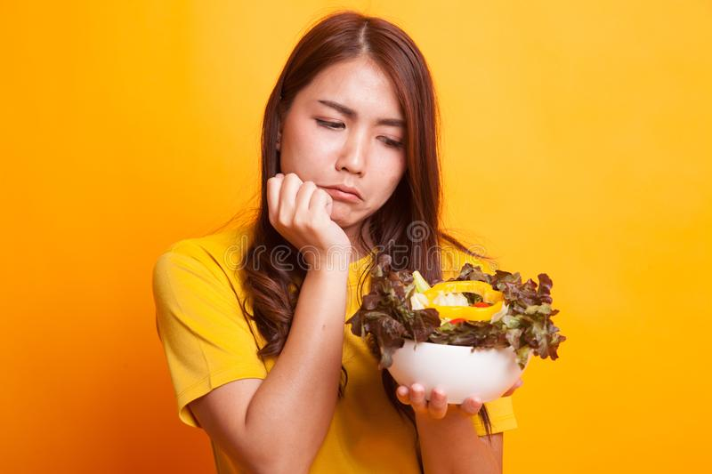Asian woman hate salad in yellow dress. Asian woman hate salad in yellow dess on yellow background royalty free stock photo