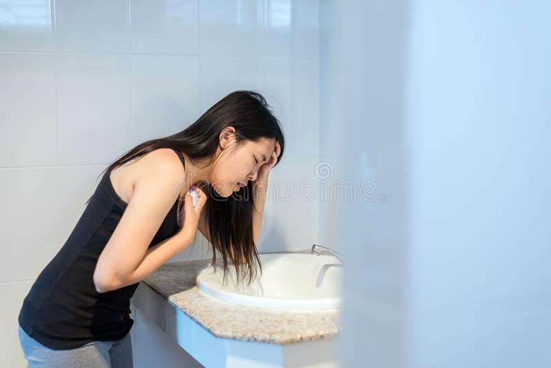 Asian woman have a morning sickness,Pregnant female nausea in toilet. After wake up stock image