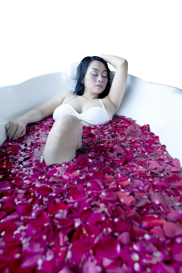 Asian woman having a bath with roses royalty free stock images