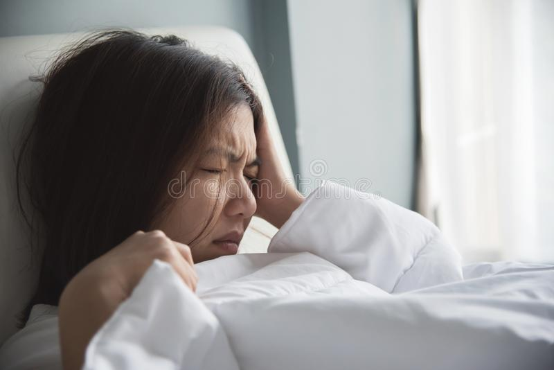 Asian woman having headache on her bed. Migraine. Illness, disease concept. stock images