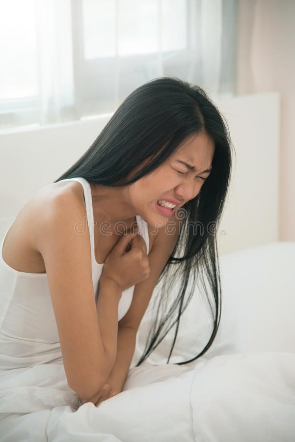 Asian woman having heart attack on her bed. stock image